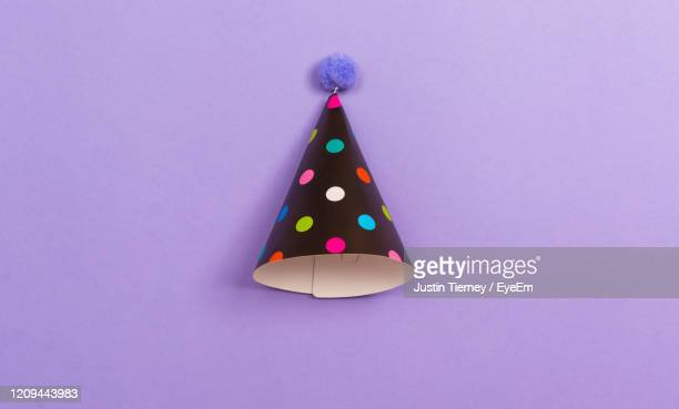 directly above shot of party hat over purple background - multi colored hat stock pictures, royalty-free photos & images