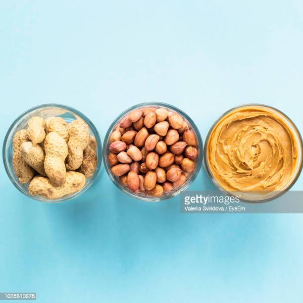 Directly Above Shot Of Peanuts In Glasses Against Blue Background