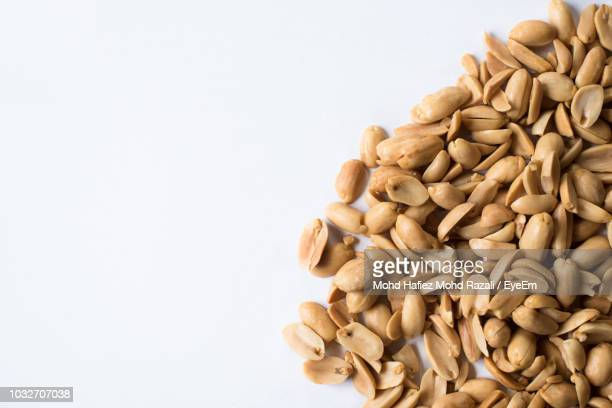 directly above shot of peanuts on white background - peanuts stockfoto's en -beelden