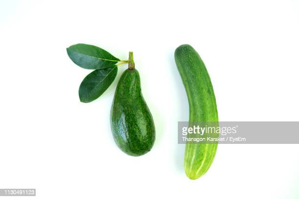 directly above shot of pear and cucumber against white background - gurke stock-fotos und bilder