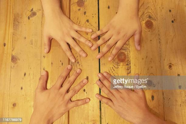directly above shot of people hands on table - jeffrey roque stock photos and pictures