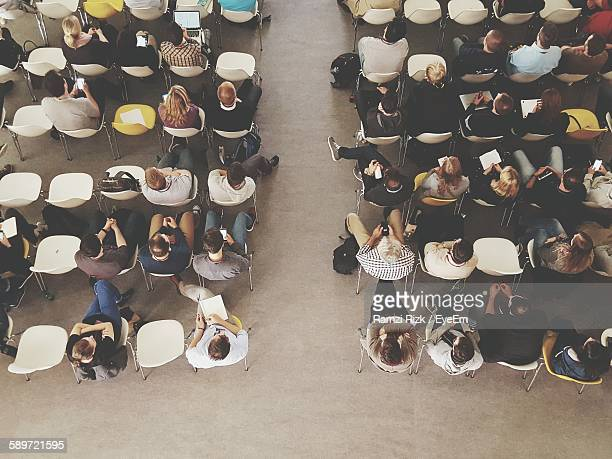 directly above shot of people sitting in auditorium - zuschauerraum stock-fotos und bilder