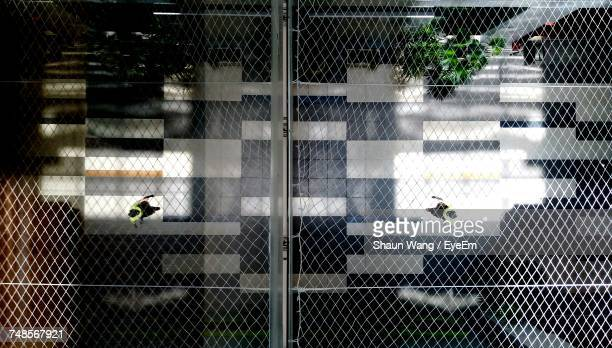 Directly Above Shot Of People Walking On Street Seen Through Metal Grate