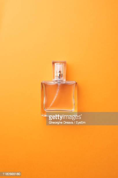 directly above shot of perfume sprayer against orange background - perfume stock pictures, royalty-free photos & images