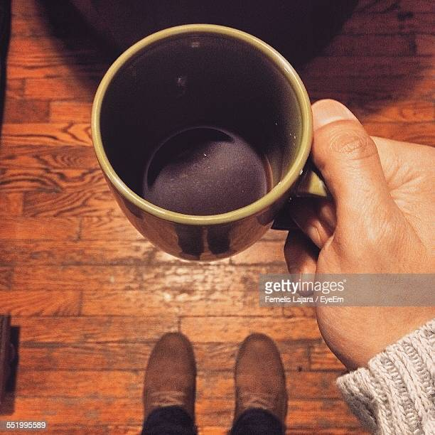 Directly Above Shot Of Person Hand Holding Black Coffee Mug