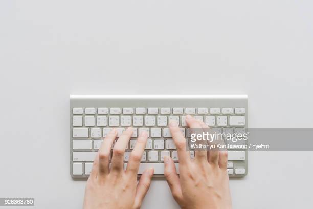 directly above shot of person hands typing on computer keyboard - computer keyboard stock pictures, royalty-free photos & images
