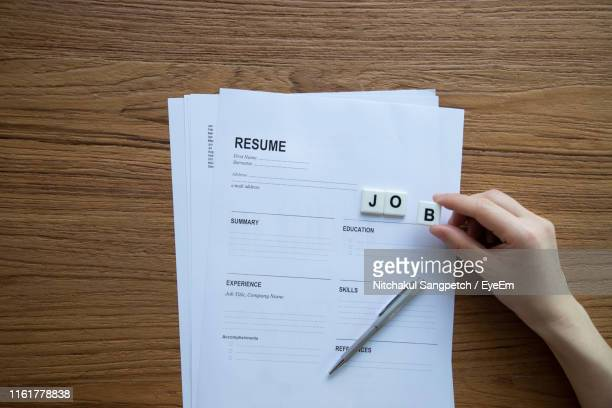 directly above shot of person holding alphabet block over resume on wooden table - the_writer's_block stock pictures, royalty-free photos & images