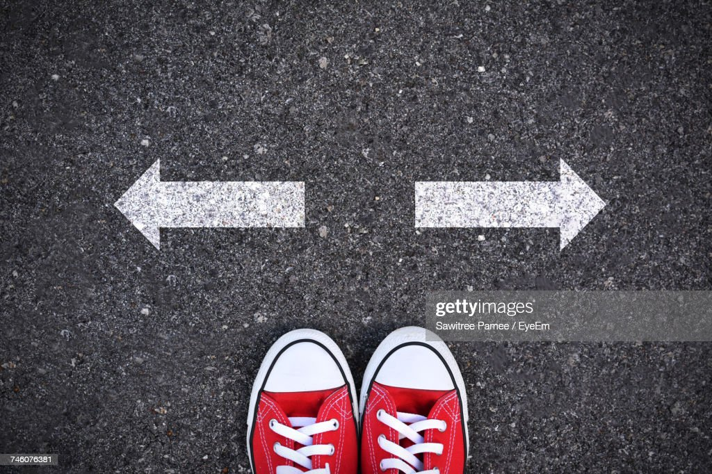 Directly Above Shot Of Person In Red Canvas Shoes By Arrow Signs In Opposite Direction On Road : Stock Photo