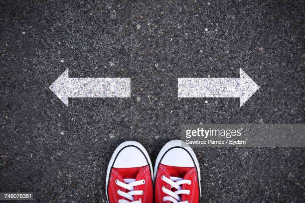 directly above shot of person in red canvas shoes by arrow signs in opposite direction on road - decisions imagens e fotografias de stock