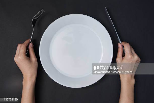 directly above shot of person with empty plate and eating utensil against black background - messer stock-fotos und bilder