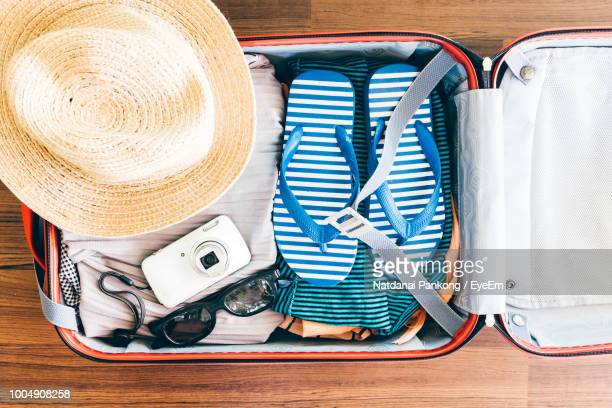 directly above shot of personal accessories in suitcase on hardwood floor - pack fotografías e imágenes de stock