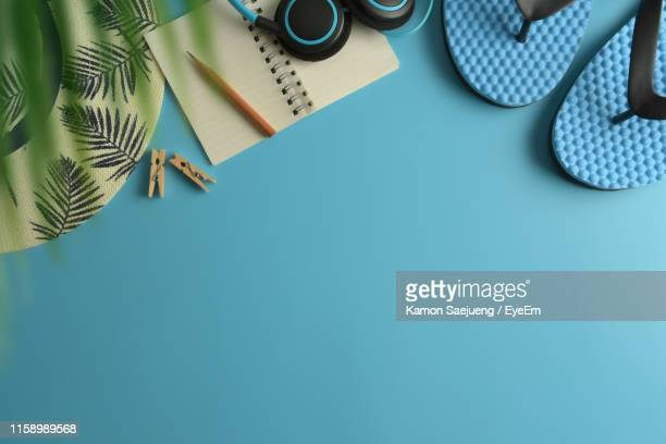 directly above shot of personal accessories on blue background - flip flop stock pictures, royalty-free photos & images