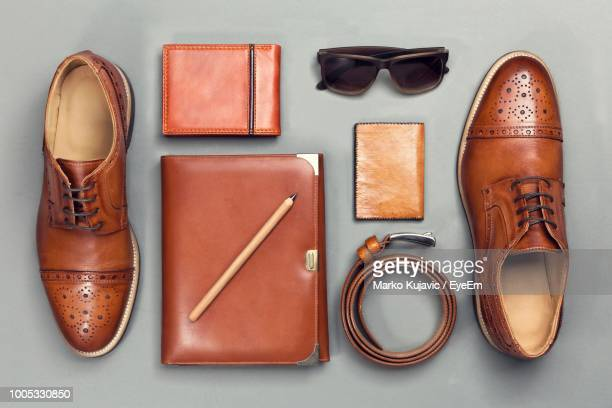 directly above shot of personal accessories on gray background - brown shoe stock photos and pictures