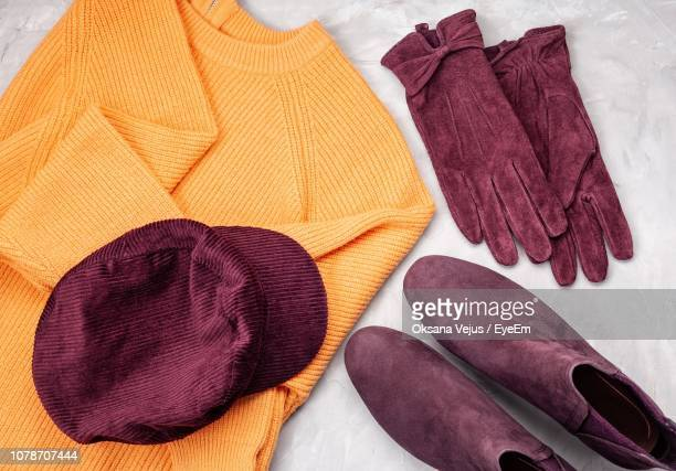 directly above shot of personal accessories on table - purple glove stock pictures, royalty-free photos & images