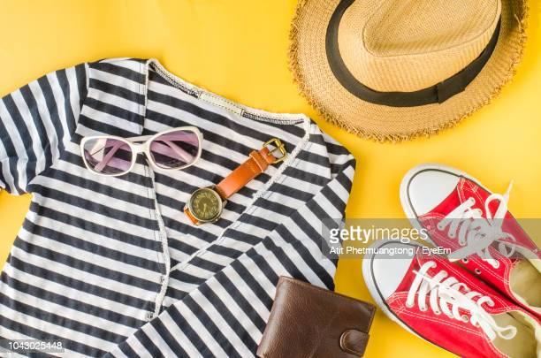 directly above shot of personal accessories on yellow background - womenswear stock pictures, royalty-free photos & images