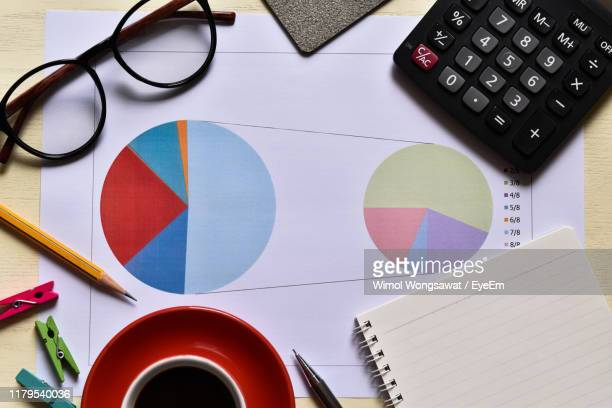 directly above shot of pie charts with office supplies on desk in office - wimol wongsawat stock photos and pictures