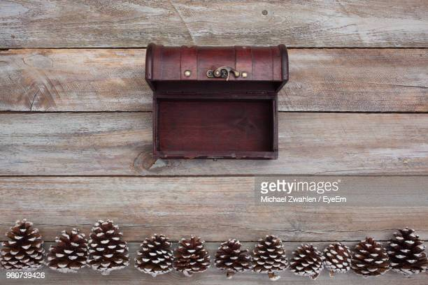 Directly Above Shot Of Pine Cones By Chest On Wooden Table