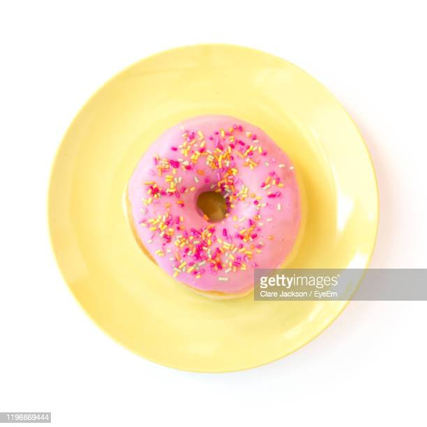 directly above shot of pink donut in plate over white background - plate stock pictures, royalty-free photos & images