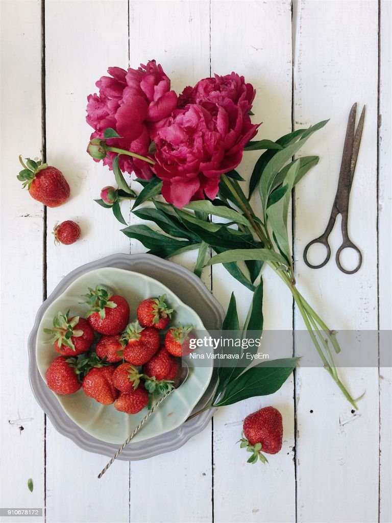Directly above shot of pink flowers with strawberries on table stock directly above shot of pink flowers with strawberries on table stock photo mightylinksfo