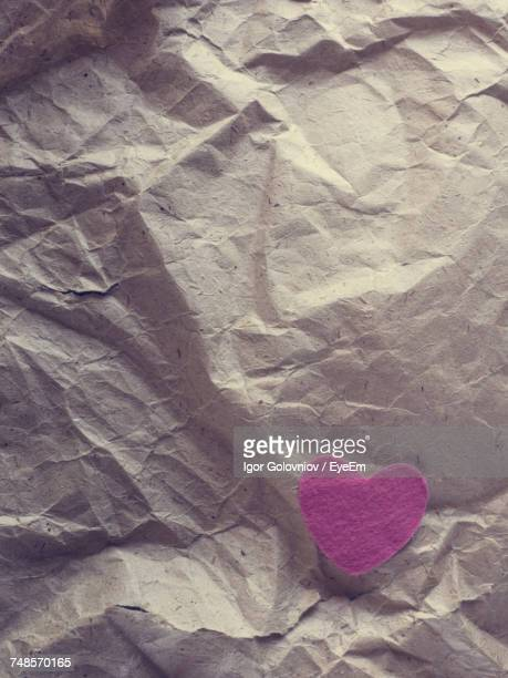 directly above shot of pink heart shape on crumpled paper - igor golovniov stock pictures, royalty-free photos & images