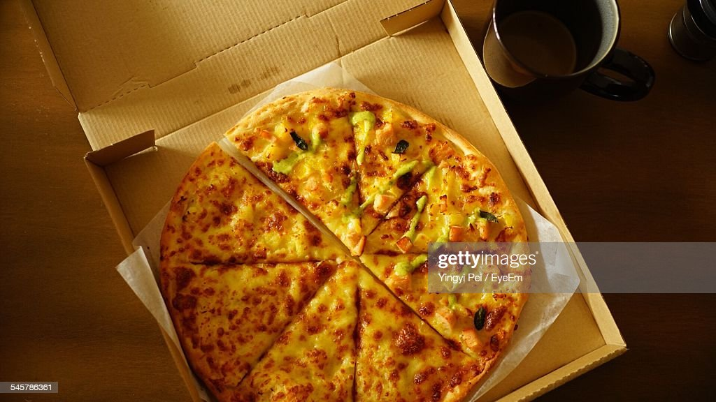 Directly Above Shot Of Pizza And Tea Cup On Table : Stock Photo