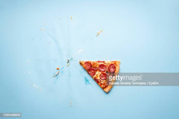 directly above shot of pizza slice on blue background - slice stock pictures, royalty-free photos & images