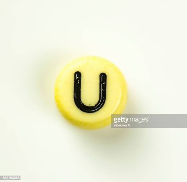 directly above shot of plastic capital letter u on white background - letter u stock photos and pictures