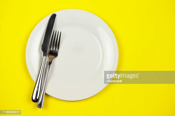 directly above shot of plate with fork and table knife - silverware stock pictures, royalty-free photos & images