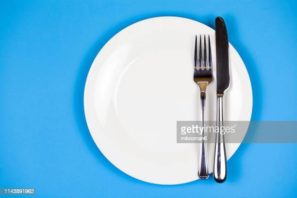directly above shot of plate with fork and table knife - plate stock pictures, royalty-free photos & images