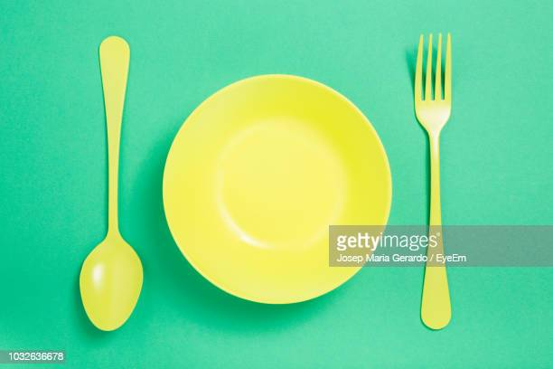 directly above shot of plate with spoon and fork on green background - eating utensil stock pictures, royalty-free photos & images