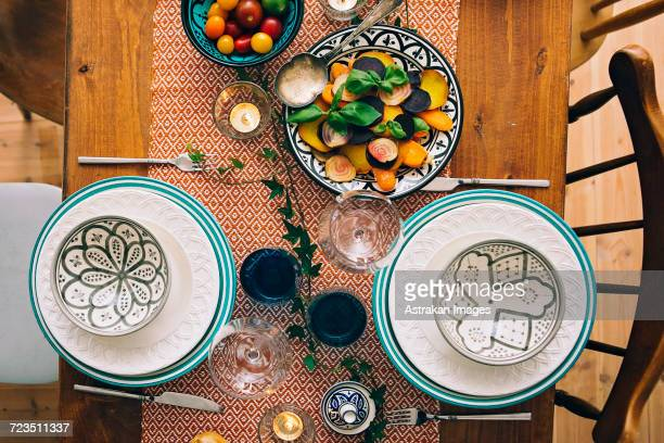 Directly above shot of plates and bowls on laid table at home