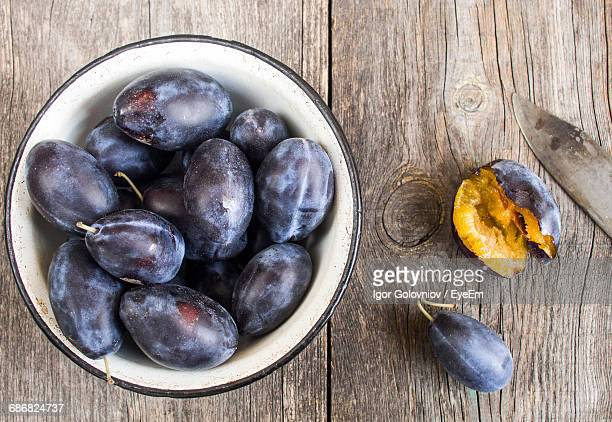 directly above shot of plums in bowl on wooden table - igor golovniov stock pictures, royalty-free photos & images