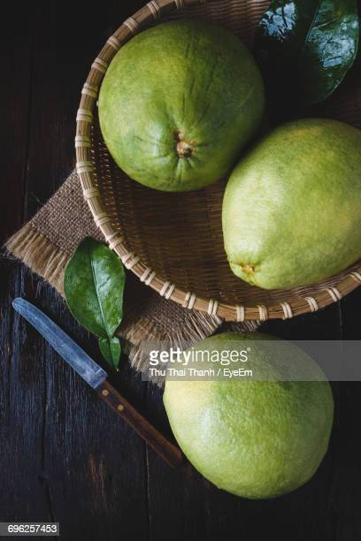 Directly Above Shot Of Pomelos And Knife On Wooden Table
