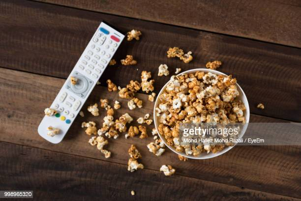 directly above shot of popcorns in bowl on wooden table - remote control stock pictures, royalty-free photos & images