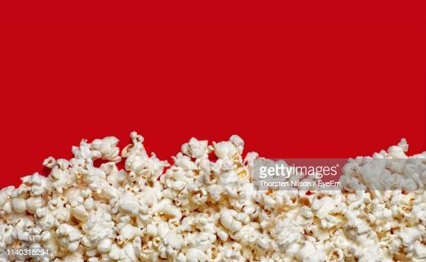 directly above shot of popcorns on red background - popcorn stock pictures, royalty-free photos & images
