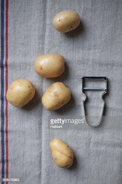 directly above shot of potatoes and peeler on napkin - dunschiller stockfoto's en -beelden
