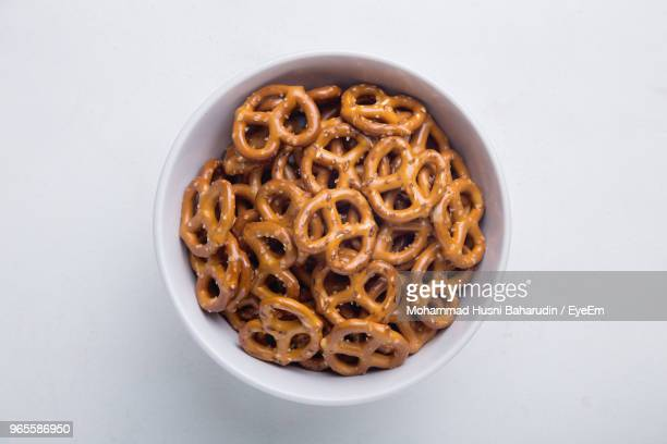 directly above shot of pretzels in bowl on white background - snack stock pictures, royalty-free photos & images