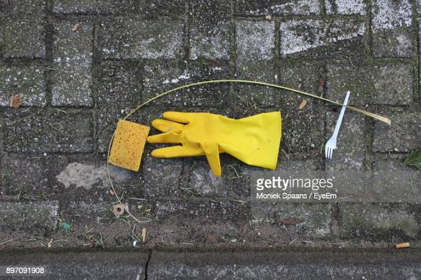 Directly Above Shot Of Protective Glove And Sponge On Footpath