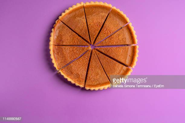 directly above shot of pumpkin pie on purple background - パイ ストックフォトと画像