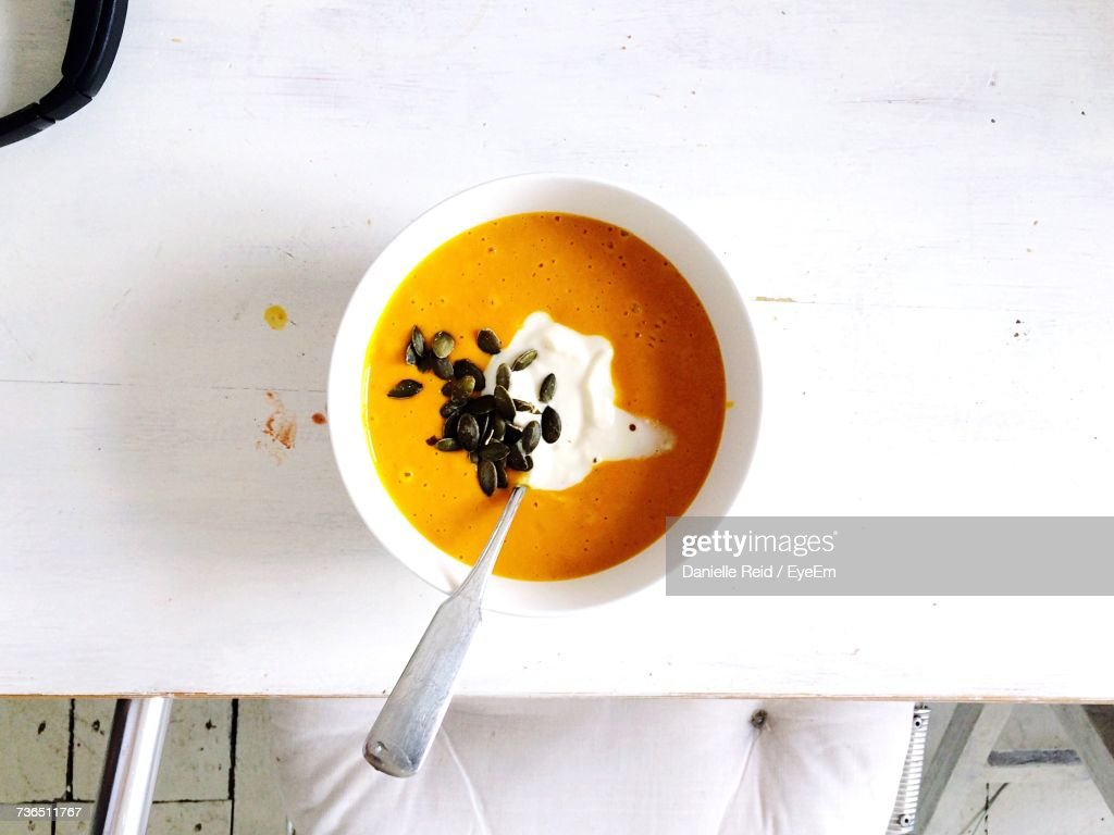 Directly Above Shot Of Pumpkin Soup In Bowl On White Table : Stock-Foto