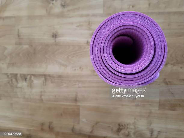 directly above shot of purple exercise mat rolled on hardwood floor - mat stock pictures, royalty-free photos & images