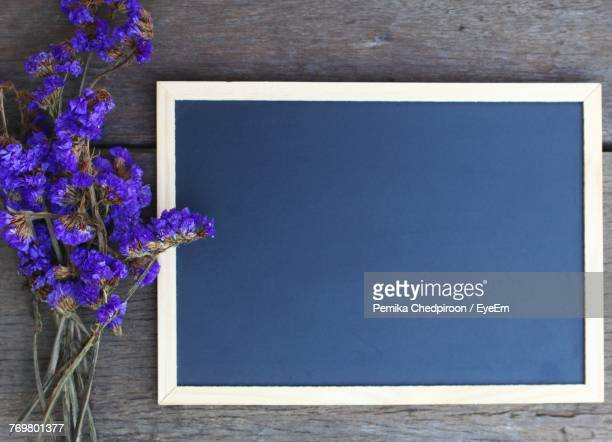 Directly Above Shot Of Purple Flower By Blackboard On Table