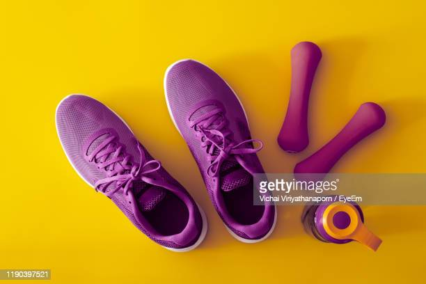 directly above shot of purple shoes with water bottles and dumbbells over yellow background - purple shoe stock pictures, royalty-free photos & images