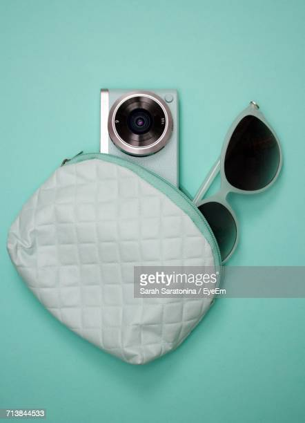 Directly Above Shot Of Purse And Digital Camera With Sunglasses Against Blue Background