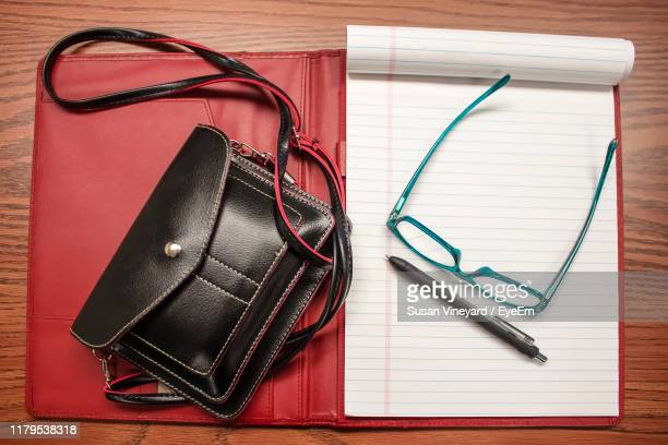 directly above shot of purse with eyeglasses on open book at table - sac à main rouge photos et images de collection