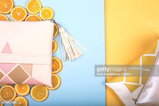 Directly Above Shot Of Purses With Orange Slices On Table