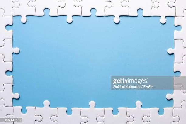 directly above shot of puzzle on blue background - jigsaw piece stock pictures, royalty-free photos & images