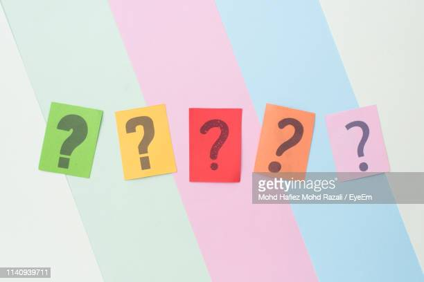 directly above shot of question marks on colorful papers on table - question mark stock pictures, royalty-free photos & images