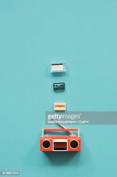 Directly Above Shot Of Radio With Cassette Against Turquoise Background