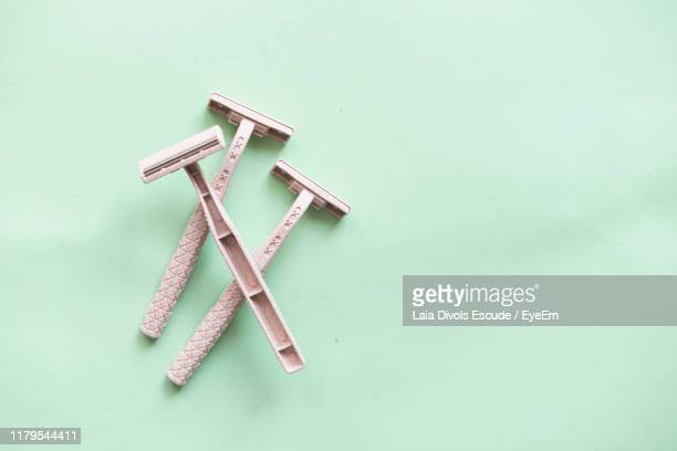 directly above shot of razors on green background - razor stock pictures, royalty-free photos & images